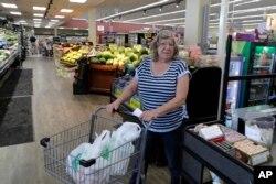 Laurie Mahlenbrei mendorong kereta berisi belanjaan setelah berbelanja di sebuah toko di Tenino, Washington, 4 Juni 2020. Laurie membayar belanjaan dengan uang kayu senilai $25. (Foto: AP)