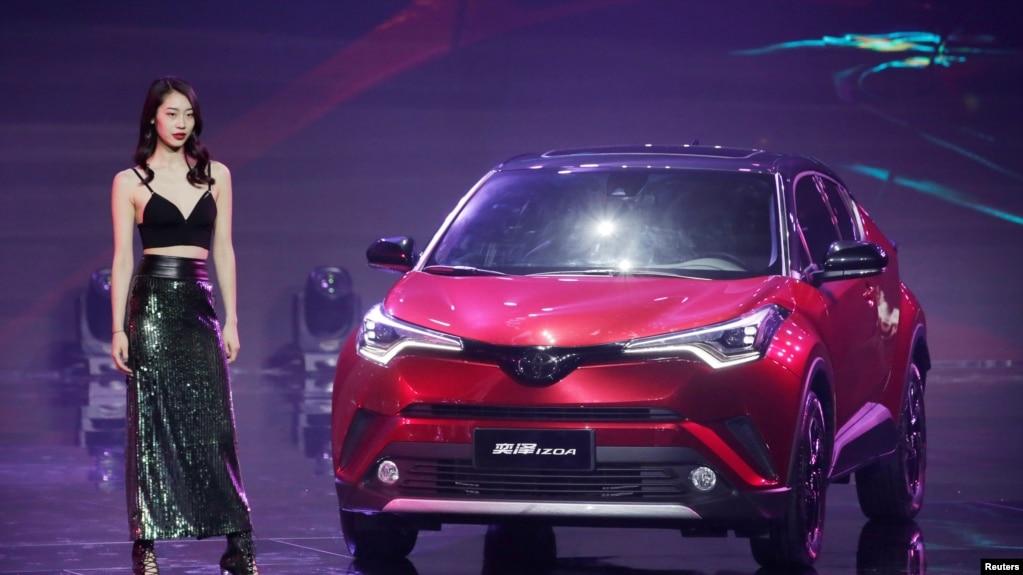 2018年4月24日,在北京車展舉行之前的啟動儀式上,車模站在豐田IZOA 汽車旁邊。 美國汽車製造商聯盟估計,對進口商品徵收25%的關稅將使每輛新汽車的平均價格上升5800美元。