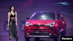 2018年4月24日,在北京车展举行之前的启动仪式上,车模站在丰田 IZOA 汽车旁边。美国汽车制造商联盟估计,对进口商品征收25%的关税将使每辆新汽车的平均价格上升5800美元。