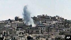 20일 시리아 정부군과 반군간 교전이 계속되는 가운데 화염이 치솟는 홈스 시.