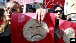 Women hold signs, with bread taped on them, demonstrate against the government in Amman, Jordan, 14 Jan 2011