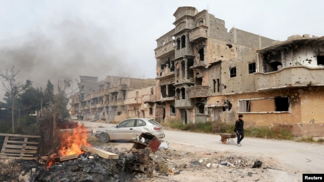 A man pulls a wheelbarrow past destroyed buildings after clashes between forces loyal to Libya's eastern government and Islamist fighters, in Benghazi, Feb. 28, 2016. Islamic State militants have expanded their control amid Libya's strife.