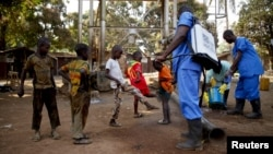 Children come forward to get their feet disinfected after Red Cross workers explained that they were spraying bleach, and weren't spraying the village with the Ebola virus, in Guinea's Forecariah district, Jan. 30, 2015.