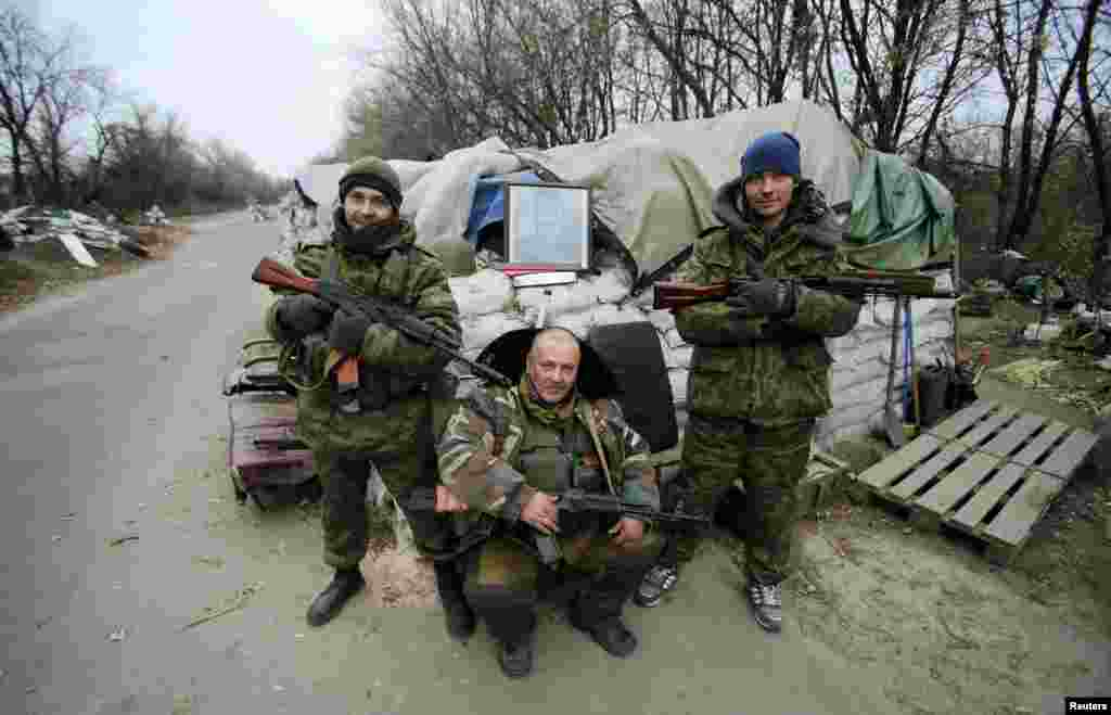 Pro-Russian separatists pose with a picture of Josef Stalin at checkpoint in the Spartak area near the Sergey Prokofiev International Airport in Donetsk, Nov. 18, 2014.