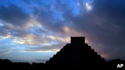 FILE - The sun rises behind Kukulkan temple in the Mayan ruins of Chichen Itza, Mexico, Dec. 2012.