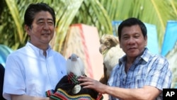 Philippine President Rodrigo Duterte, right, hands over a Philippine Eagle stuffed toy named Sakura to Japan's Prime Minister Shinzo Abe during the ceremonial eagle naming at the garden area of Waterfront Insular Hotel in Davao City, southern Philippines,