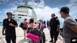 This photo provided by the Dutch Defense Ministry on Sept. 10, 2017, shows people walking toward a cruise ship anchored on St. Maarten, after the passage of Hurricane Irma.