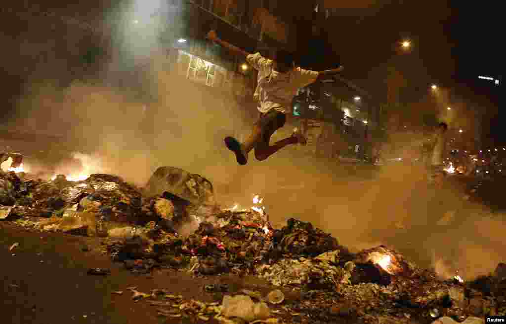 A boy jumps over a barricade of burning garbage that supporters of opposition leader Henrique Capriles used to block a street, as they demonstrated for a recount of the votes in Sunday's election, in Caracas, April 15, 2013.
