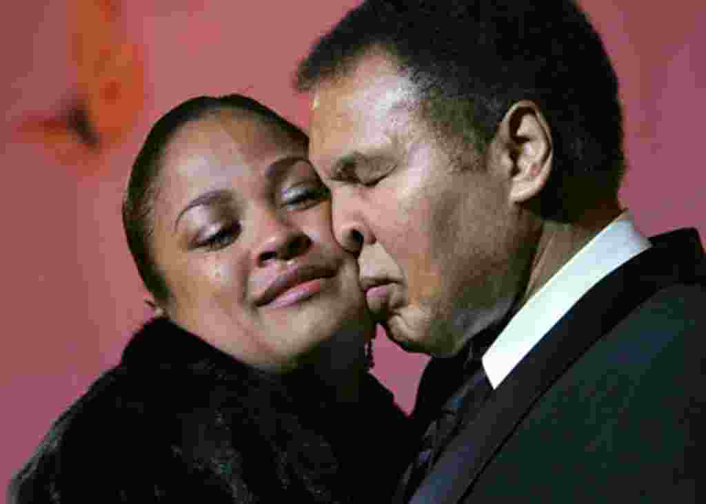 Laila Ali-McClain cries as she presses her cheek against her father, Muhammad Ali, as the two share the stage at the Butterfly Ball, a tribute to the elder Ali, coinciding with Black History Month, Saturday, Feb., 26, 2005, in Atlanta. (AP Photo/John Amis