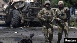 Tentara NATO mengamankan lokasi serangan bom mobil di Kabul, Afghanistan, Selasa (30/6).