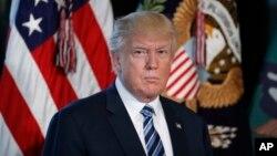 President Donald Trump listens as Treasury Secretary Steve Mnuchin speaks at the Treasury Department in Washington, April 21, 2017.