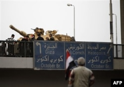 An anti-government protester looks towards an Egyptian tank on a bridge near Tahrir, or Liberation square in Cairo, Egypt, Thursday, Feb. 3, 2011. (AFP PHOTO)
