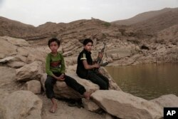 "In this July 30, 2018, photo, a 17 year-old boy holds his weapon in High dam in Marib, Yemen. Experts say child soldiers are ""the firewood"" in the inferno of Yemen's civil war, trained to fight, kill and die on the front lines. (AP Photo/Nariman El-Mofty)"