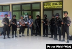 Sejumlah polisi berjaga di depan ruang jenazah RS Bhayangkara Polda Jawa Timur (Foto: VOA/Petrus Riski).