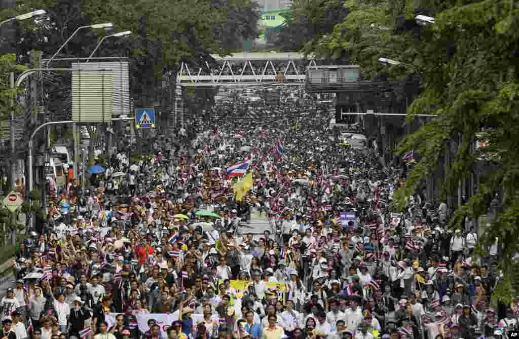 Anti-government demonstrators pour into the street while chanting slogans during a rally against an amnesty bill in Bangkok, Nov. 11, 2013.