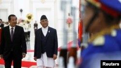 នាយករដ្ឋមន្ត្រីប្រទេសនេប៉ាល់ លោកខាត់ហ្គា ប្រាសាត សាម៉ា អូលី (Khadga Prasad Sharma Oli) ដើរអមលោកនាយករដ្ឋមន្ត្រី ហ៊ុន សែន កាន់ក្បួនព្យុហយាត្រា នៅក្នុងជំនួបពិភាក្សាគ្នាមួយ នៅវិមានសន្តិភាព រាជធានីភ្នំពេញ ថ្ងៃទី១៣ ខែឧសភា ឆ្នាំ២០១៩។ (REUTERS/Samrang Pring)