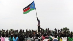 A man holds up South Sudan's new flag as South Sudanese children rehearse their dance routine, to be performed at half time during South Sudan's national soccer team's match with Kenya as part of the independence day celebrations. Photo by Paul Banks,