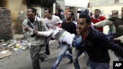 Egyptians carry an injured protester during clashes with anti-riot police in Cairo, Egypt, Saturday, Jan. 29, 2011.