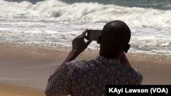 Un curieux photographie les vagues sur la côte du village d'Afidégnigba au Togo, 19 septembre 2018. (VOA/Kayi Lawson)