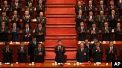 Chinese President Xi Jinping, front row center, applauds with party members during the Communist song at the closing ceremony for the 19th Party Congress at the Great Hall of the People in Beijing, Tuesday, Oct. 24, 2017. (AP Photo/Andy Wong))