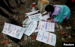 A student writes placards before a protest march demanding protection for the Amazon rainforest near the consulate of Brazil in Kolkata, India, August 26, 2019.