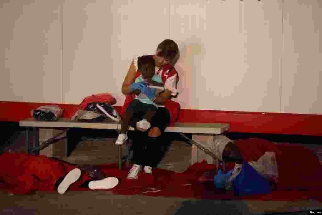 بازی کردن یکی از اعضای صلیب سرخ اسپانیا با یک کودک مهاجرکه توسط یک قابق نجات به بندر مالاگا در جنوب اسپانیا رسید.