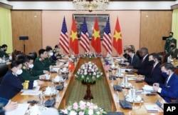 U.S Defense Secretary Lloyd Austin, third from right, and Vietnamese Defense Minister Phan Van Giang, third from left, hold a meeting in Hanoi, Vietnam, Thursday, July 29, 2021. (Nguyen Trong Duc/VNA via AP)
