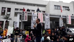 FILE - A professor speaks to students during a protest outside Taiwan's legislature in Taipei, March 20, 2014.