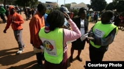 Zimbabwe Electoral Commission officials conducting an election campaign exercise outside Mai Musodzi Hall in Mbare,Harare.