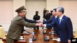 South Korean National Security Director, Kim Kwan-jin, right, and Unification Minister Hong Yong-pyo, second from right, shake hands with Hwang Pyong So, left, North Korea' top political officer for the Korean People's Army, and Kim Yang Gon, a senior Nor