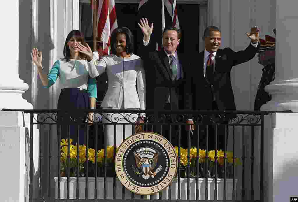 The Obamas wave with the Camerons from the South Portico balcony of the White House during an official arrival ceremony for the British leader and his wife. (AP)
