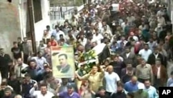 Syrian Arab News Agency (SANA) handout photo shows people gathering for funeral of two people allegedly killed in recent clashes in Homs, north of Damascus on Apr 19 2011