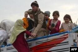 Keluarga pengungsi Afghanistan naik ke truk yang membawa mereka kembali ke negara asal mereka di pusat repatriasi Komisaris Tinggi PBB untuk Pengungsi (UNHCR) di pinggiran Peshawar, 1 Maret 2018. (AFP)