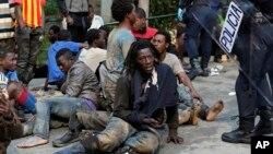17일 스페인 영토 세우타 지역를 무단 진입한 모로코 난민들 주변에서 스페인 경찰이 대기하고 있다.