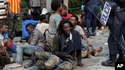 Des migrants sont surveillés par la police espagnole dans l'enclave de Ceuta, Espagne, le 17 février 2017.