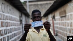 FILE - A man displays a sample 100 franc note in a fictional Ivorian currency, in Abidjan, Ivory Coast, Jan. 8, 2011. Some analysts argue Ivory Coast is among regional countries strong enough to break off on their own.