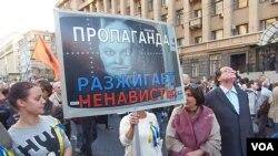 """去年秋季莫斯科的一场主张和平反战大游行中,示威者手举基谢廖夫画像,上面写着""""宣传煽动仇恨"""",抗议官方媒体谎言宣传。"""
