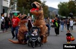 People wearing costumes walk during Halloween in Sierra Madre, California, U.S., October 31, 2017.