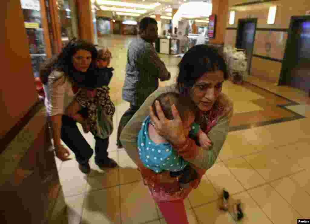 Women carrying children run for safety as armed police hunt gunmen at the Westgate Mall in Nairobi, Sept. 21, 2013.