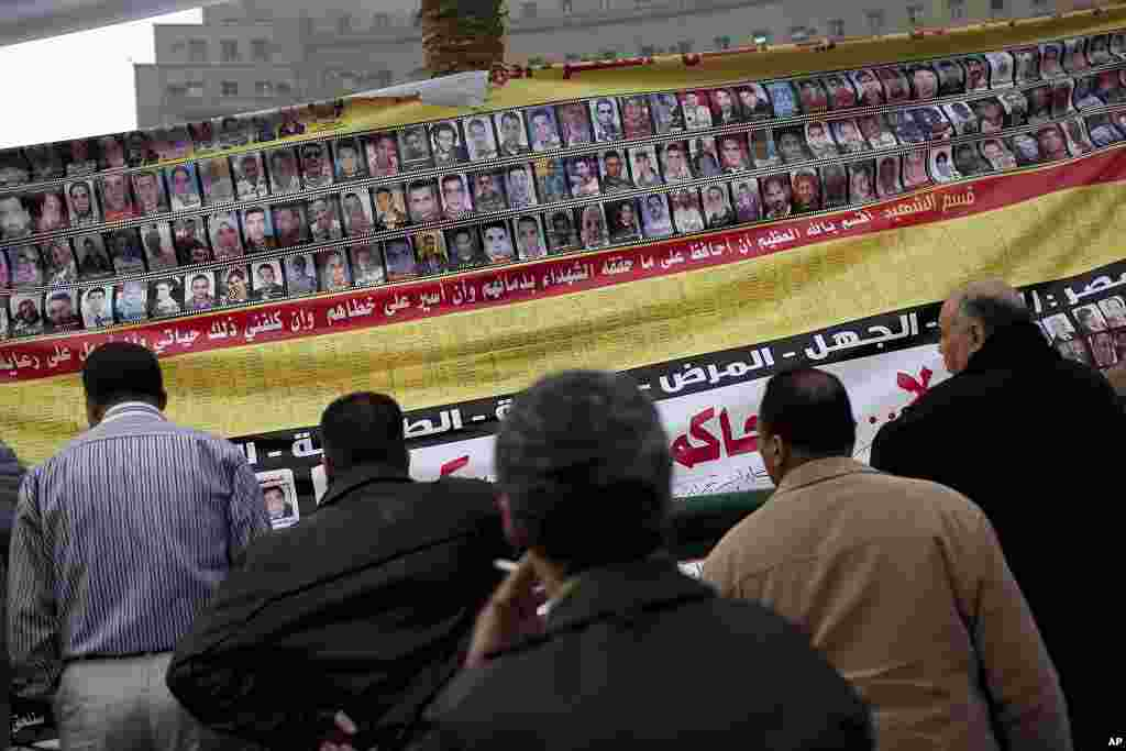 Protesters in Tahrir Square look at a banner bearing pictures of people killed during recent unrest in Cairo, Egypt, November 27, 2011. (AP)