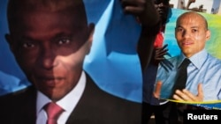 FILE - Supporters of main opposition Senegalese Democratic Party (PDS) hold posters of former Senegalese president Abdulaye Wade (L) and his son Karim (R) during a protest in Dakar, April 23, 2013.