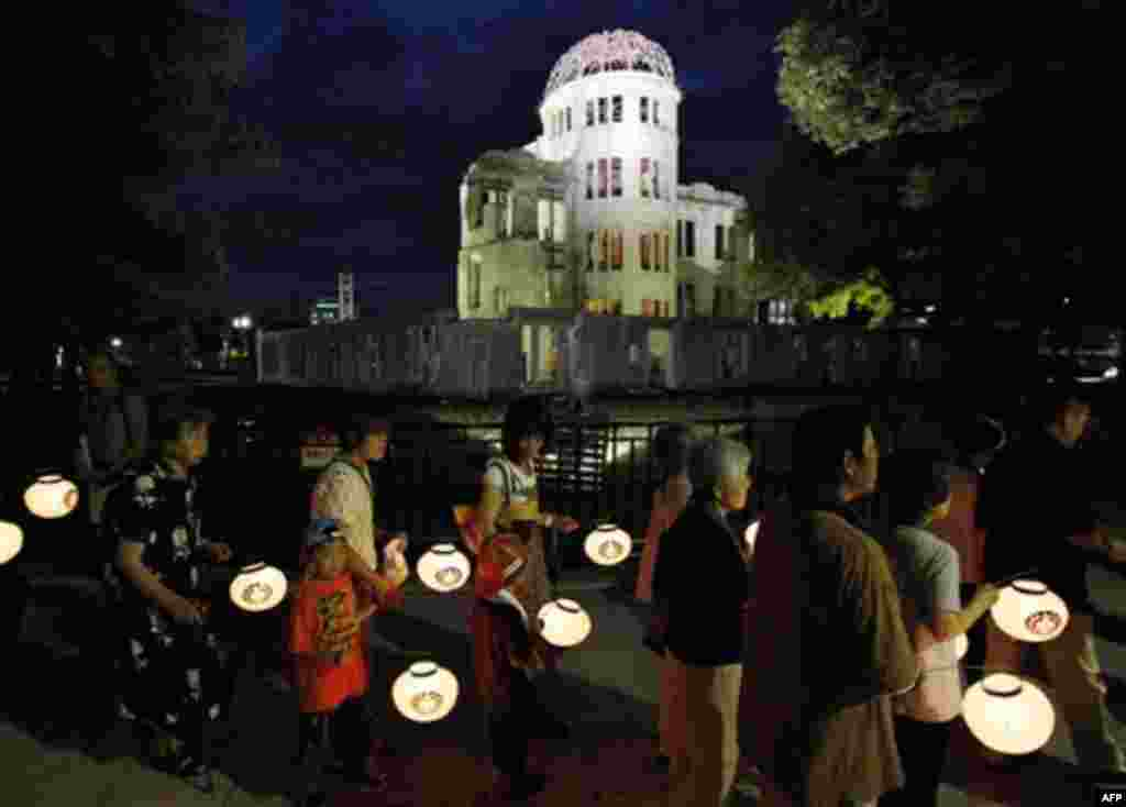 Buddhist followers parade with lanterns in their hands in prayer for peace around the illuminated Atomic Bomb Dome in Hiroshima, western Japan on the eve of the 66th anniversary of the world's first atomic bombing on the city, Friday, Aug. 5, 2011. (AP Ph