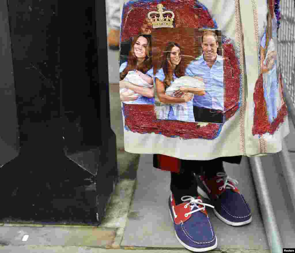 A royal fan stands outside St. James's Palace before the christening of Prince George in London, Oct. 23, 2013.