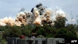 Khói cuộn lên sau rặng cây sau cuộc không kích của máy bay NATO, và các nhân chứng nói phần lớn các quả bom rơi xuống các khu vực quân sự