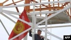 Người biểu tình cầm cờ leo lên tháp trong khuôn viên Bộ Quốc phòng Kyrgyzstan ở Bishkek