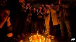 Warga menyalakan lilin dan berdoa untuk para korban penusukan di alun-alun di luar stasiun kereta api Kunming di provinsi Yunnan (2/3). (AP/Alexander F. Yuan)