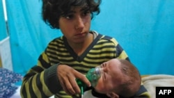A Syrian boy holds an oxygen mask over the face of an infant at a makeshift hospital following a reported gas attack on the rebel-held besieged town of Douma in the eastern Ghouta region on the outskirts of the capital Damascus. (File)