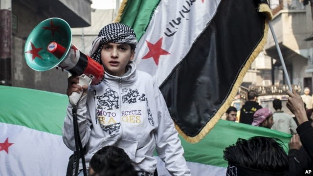 Syrian youth with megaphone leads rally supporting the Free Syrian Army in the Aleppo's Bustan al-Qasr district, January 4. (AP)