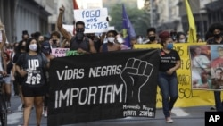 """FILE - In this June 11, 2020 file photo, people holding a banner that reads """"Black Lives Matter"""" march during a protest against racism and police violence in Niteroi, Rio de Janeiro, Brazil. (AP Photo/Silvia Izquierdo)"""