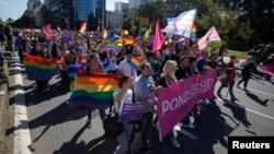 Gay rights and human rights activists march during a Pride march in Belgrade, Serbia, Sept. 28, 2014.